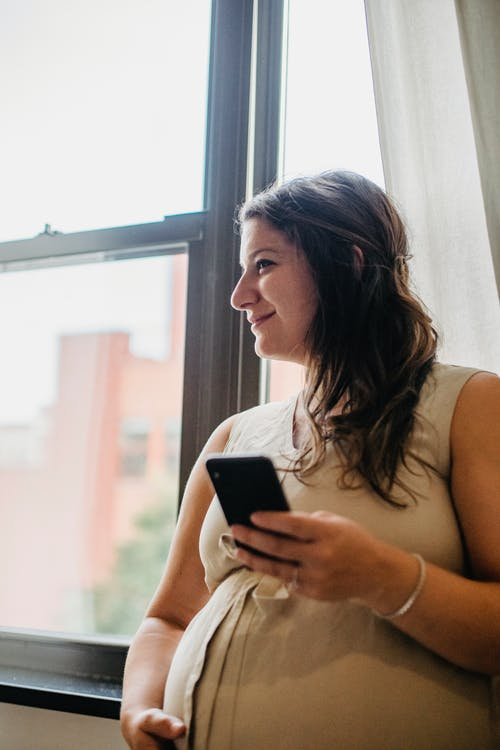 Pregnant lady using phone while standing at home