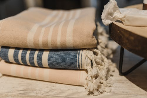 Stack of blankets placed on wooden table