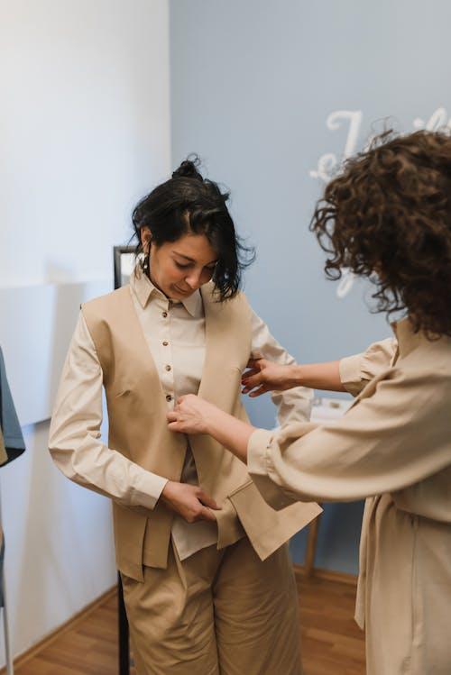 Woman in Beige Blazer Holding Woman in White Dress