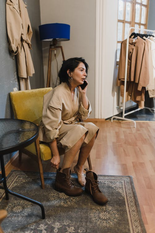 Woman in Brown Coat Sitting on Chair