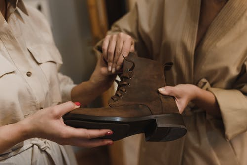 Person Holding Brown Leather Boots