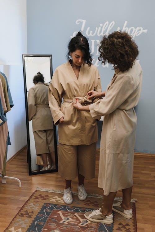 2 Women in Beige Coat Standing Beside White Wall