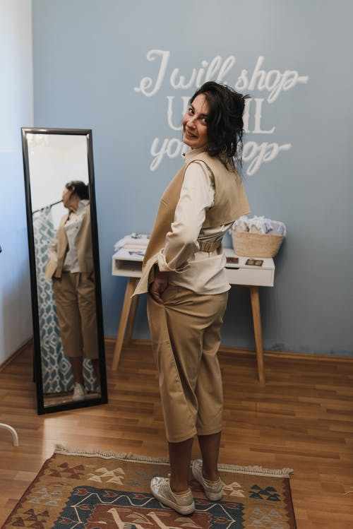 Woman in White Long Sleeve Shirt and Brown Pants Standing Beside White Wall