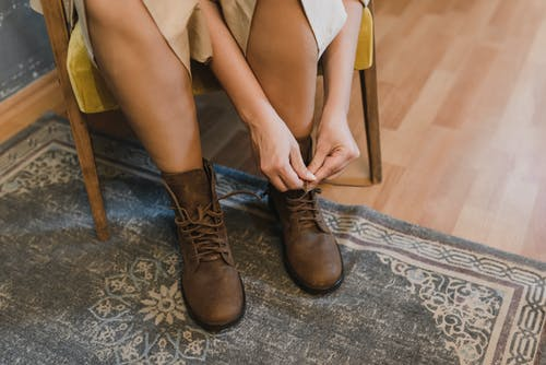 Woman in Brown Leather Boots Sitting on Brown Wooden Chair