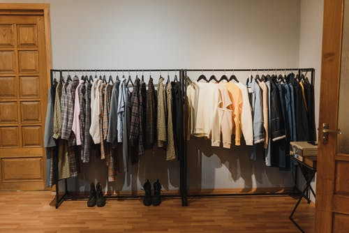 White and Black Clothes Hanging on Black Steel Rack