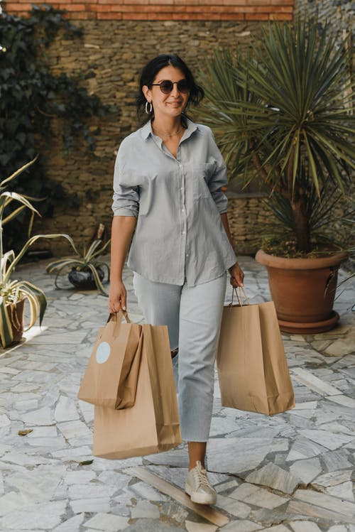 Woman in Gray Button Up Shirt and Brown Pants Holding Brown Paper Bags