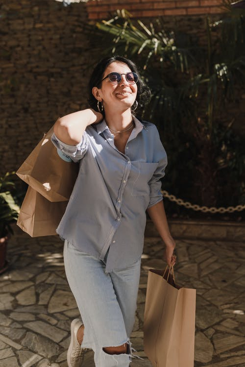 Woman in Blue Button Up Shirt and Gray Pants Holding Brown Paper Bag