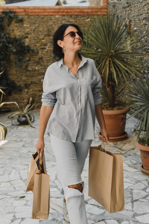 Woman in Blue Button Up Shirt and White Pants Holding Brown Paper Bags