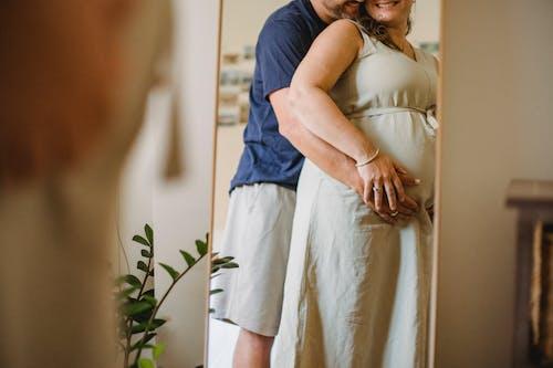 Faceless man hugging pregnant woman in light bedroom