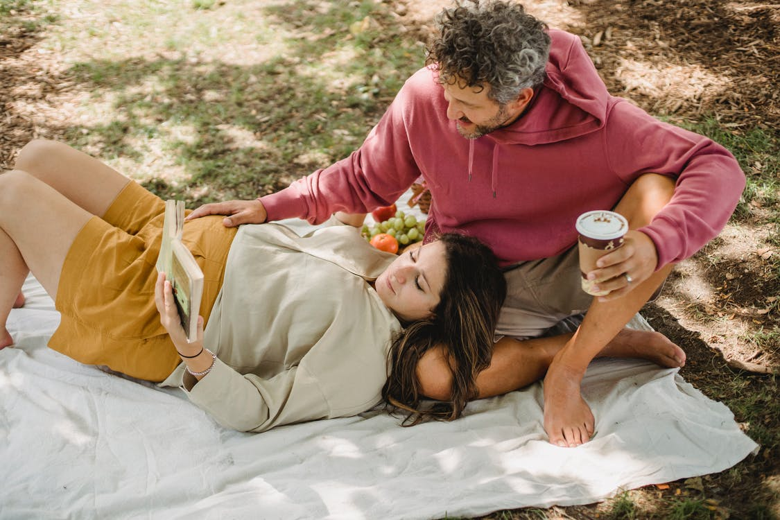 Couple resting on picnic together outdoors