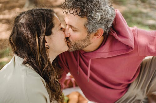 Side view of romantic wife and husband kissing each other while sitting on blanket on blurred background during picnic in nature