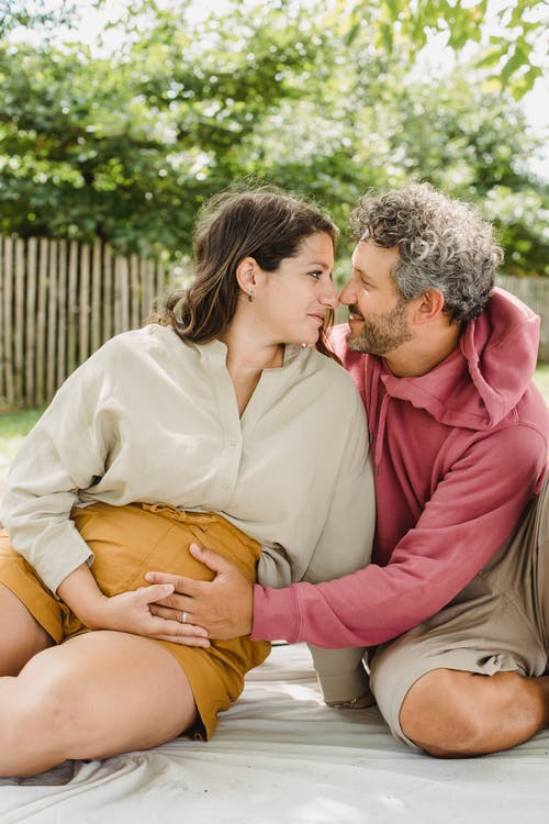 Romantic husband touching belly of pregnant wife while sitting on blanket and looking at each other in countryside during weekend