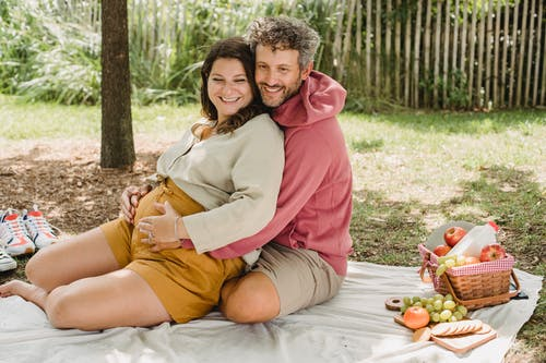 Full body of loving pregnant woman and man embracing while sitting on plaid with food and looking away during romantic moment