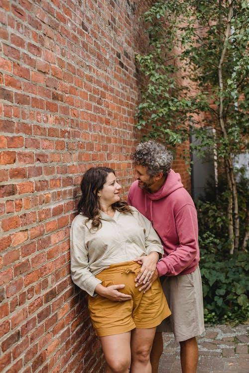 Happy adult man with gray curly hair embracing pregnant wife and touching belly while looking at eyes
