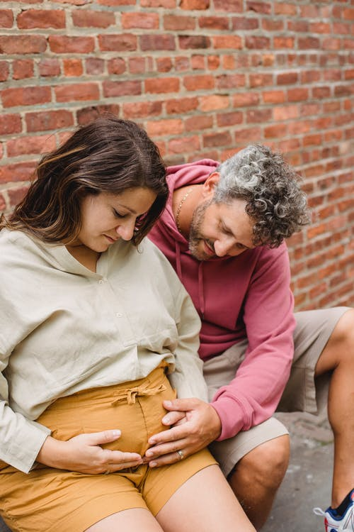 Adult male with gray curly hair touching belly of pregnant wife while sitting near brick wall