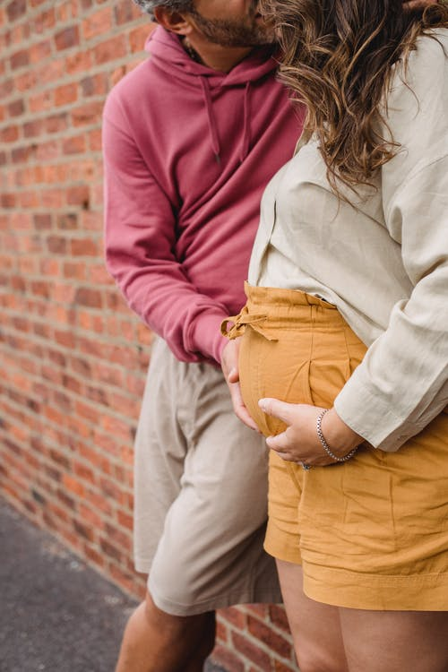 Side view of crop bearded man kissing pregnant wife with long hair near brick wall