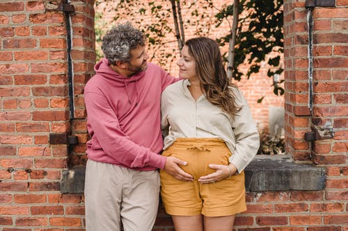 Delighted adult male with curly gray hair standing with smiling pregnant female near brick wall and touching tummy