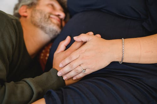 Smiling man touching belly of anonymous pregnant wife at home