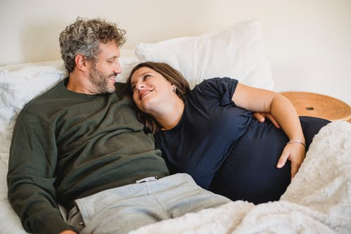 Content adult male embracing gently expectant woman while looking at each other in bed at home
