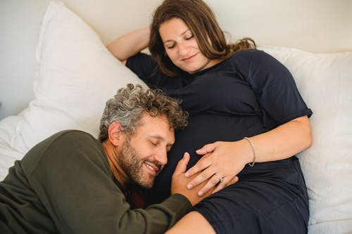 Adult smiling husband with closed eyes stroking tummy of expectant woman leaning on hand in bedroom