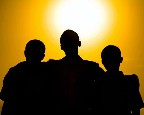 Silhouettes of faceless people hugging while standing against bright orange sky at sundown