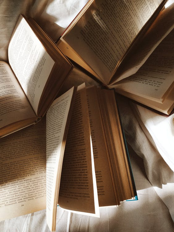 Opened books placed on white bedsheets