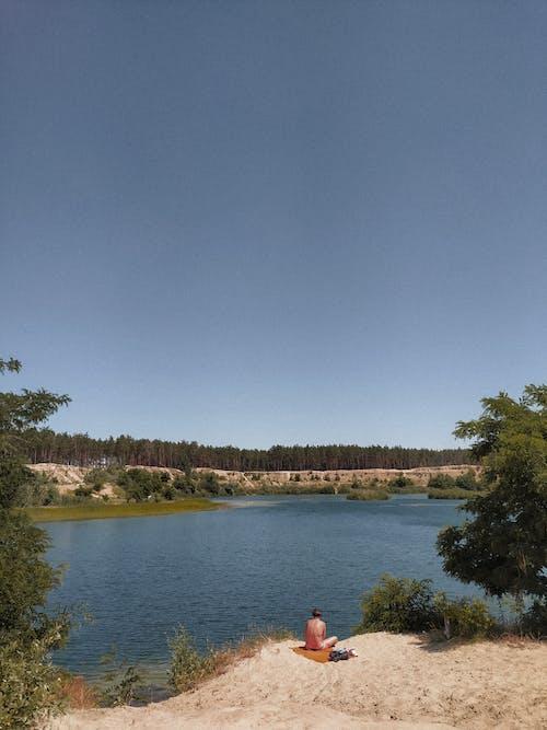 Unrecognizable person chilling on picturesque lake shore