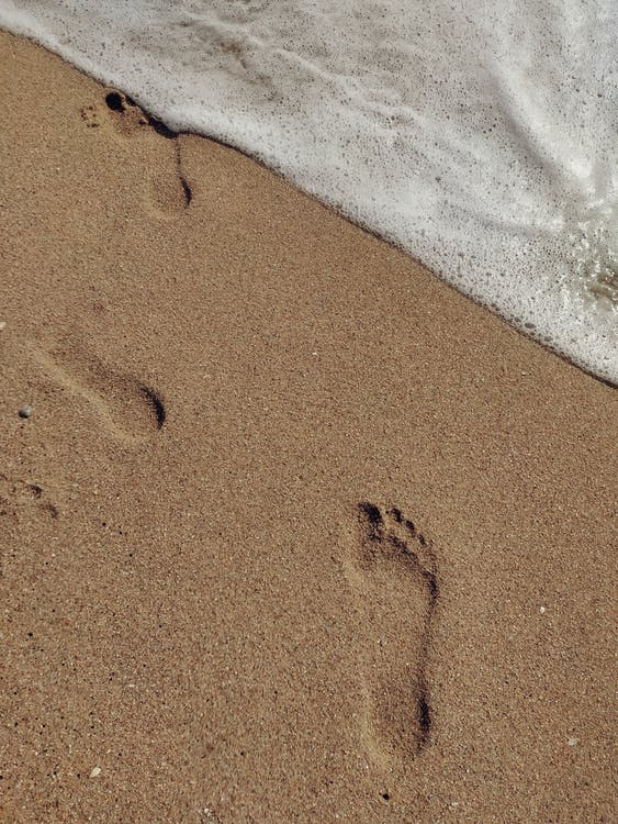 Top view barefoot human footprints left on sandy seacoast washed by foamy seawater