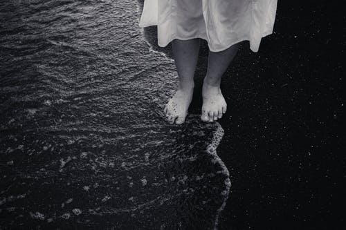 Black and white from above of crop unrecognizable barefoot female traveler in dress standing on coast near rippled ocean
