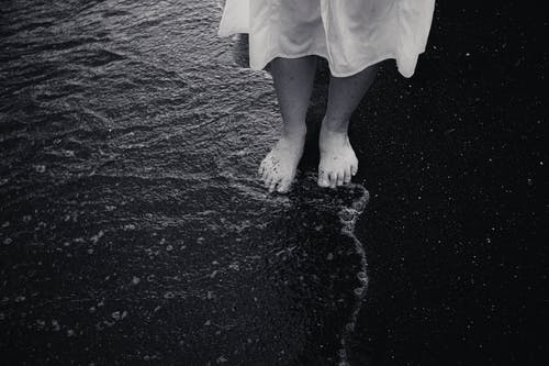 Crop female traveler on sea shore in wave water