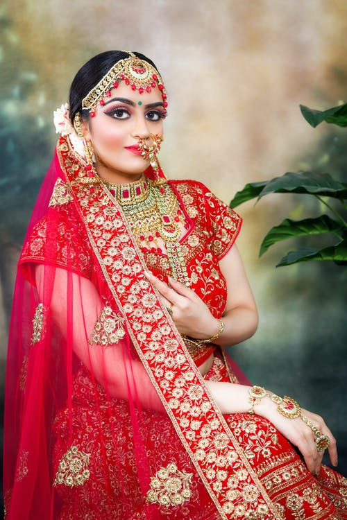 Confident young Indian woman in traditional red bridal clothes and sari with piercing and bracelets with necklace and makeup with earrings while looking at camera near green plant
