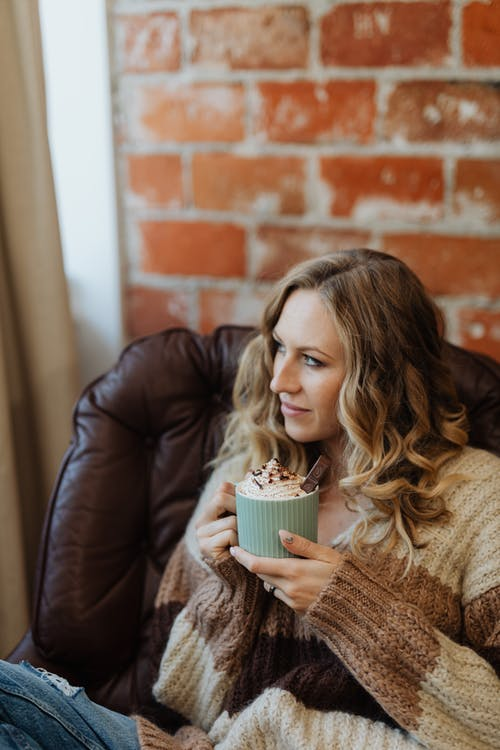 Woman in Brown Sweater Holding White Cup