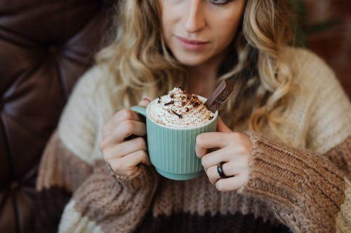 Woman in Brown Sweater Holding Green Ceramic Mug With Brown and White Liquid