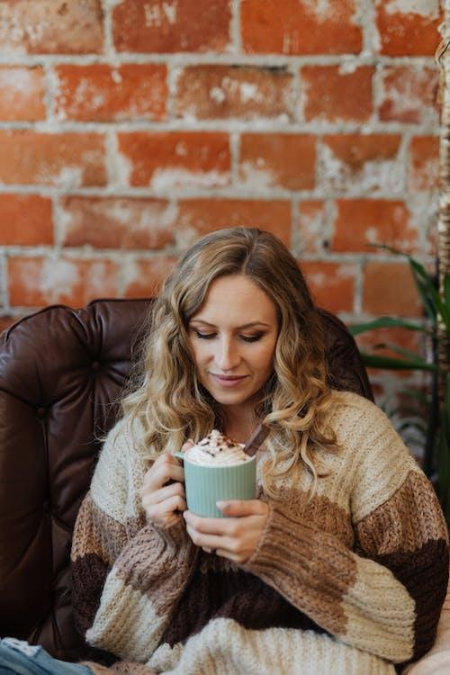Woman in Beige Sweater Holding White Ceramic Mug
