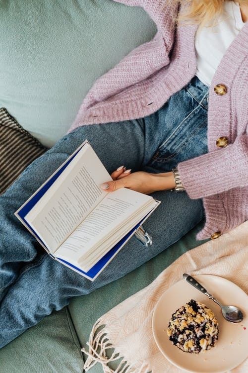 Person in Pink Sweater and Blue Denim Jeans Reading Book