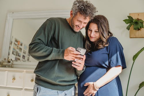 Content bearded male showing cellphone to feminine expectant woman caressing tummy in house room in sunlight