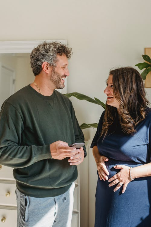 Adult smiling expectant female speaking with bearded male partner with cellphone while looking at each other in house