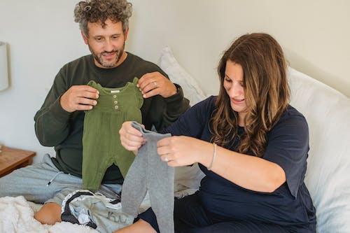 Zwangere Vrouw Met Gewas Man Kijken Naar Babykleding Op Bed