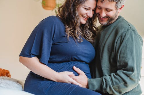Happy pregnant couple caressing on bed
