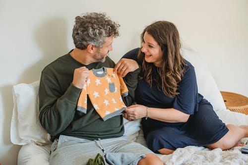Happy couple considering apparel for newborn baby