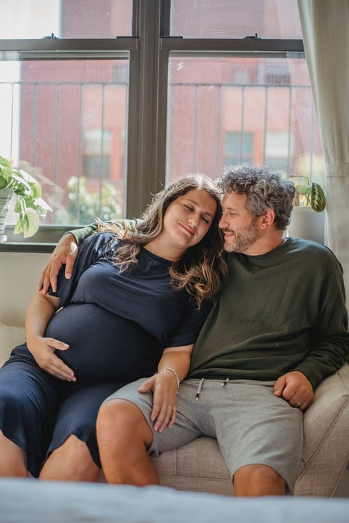 Positive husband hugging pregnant wife while sitting on sofa
