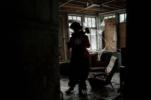 Man in Black Jacket and Black Pants Standing Inside Abandoned Building