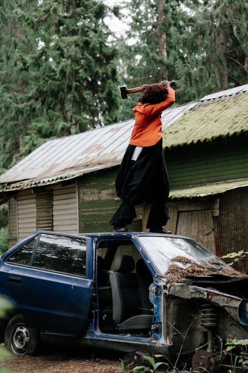 Person With a Hammer Standing on the Roof of a Car