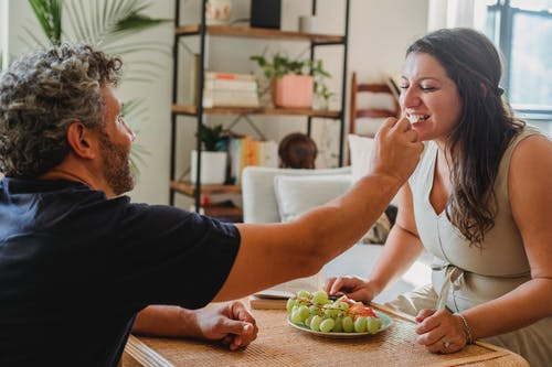 Positive adult man giving fresh grape to wife while sitting together at wicker table with various fruits in cozy apartment in daylight