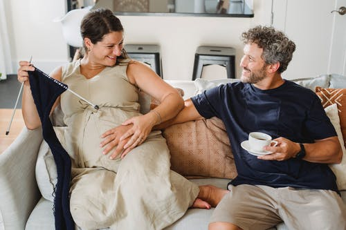 From above of smiling adult bearded man sitting on couch with hot coffee and touching pregnant belly of happy wife with knitting needles