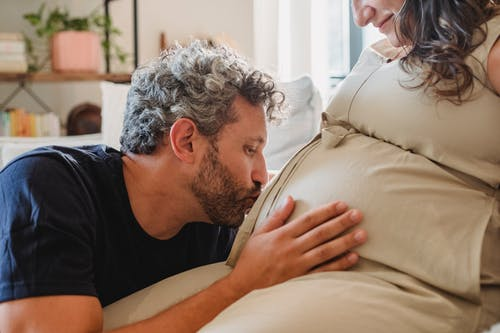 Side view of loving adult husband gently touching and kissing pregnant tummy of crop wife sitting on couch in light apartment