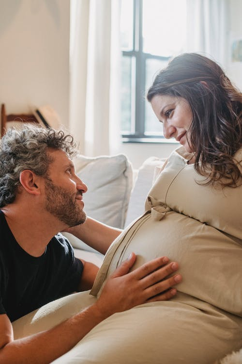 Loving pregnant couple embracing and looking at each other
