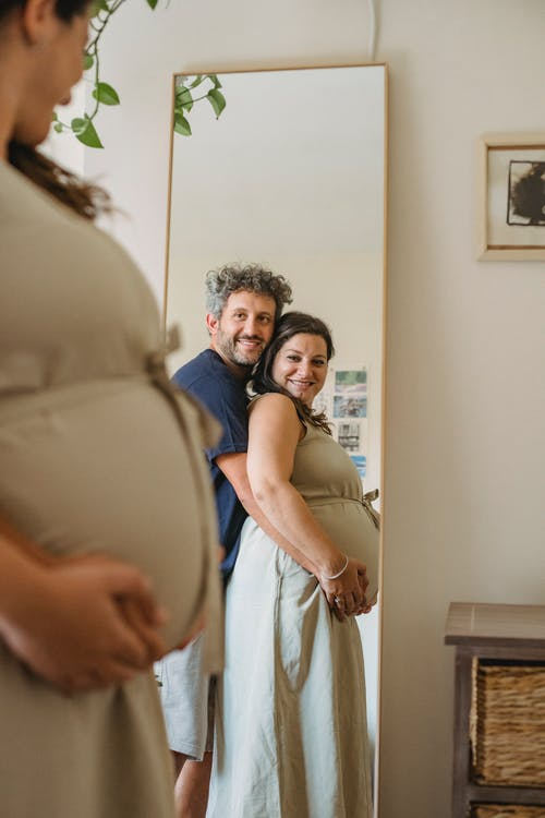 Cheerful couple touching pregnant tummy and looking in mirror