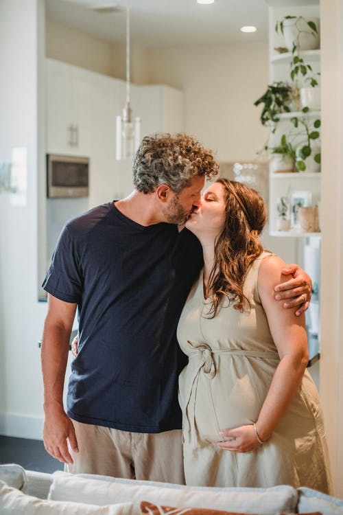 Happy adult pregnant wife and husband kissing while standing behind couch