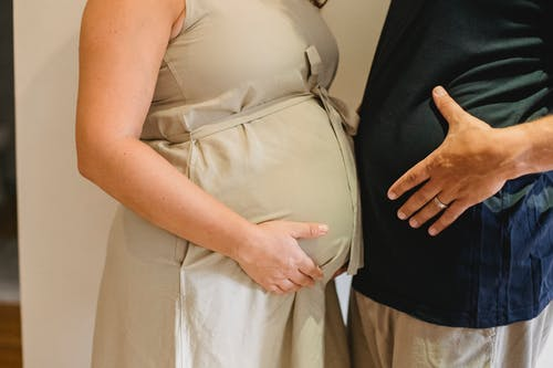 Faceless pregnant couple comparing stomachs against white wall